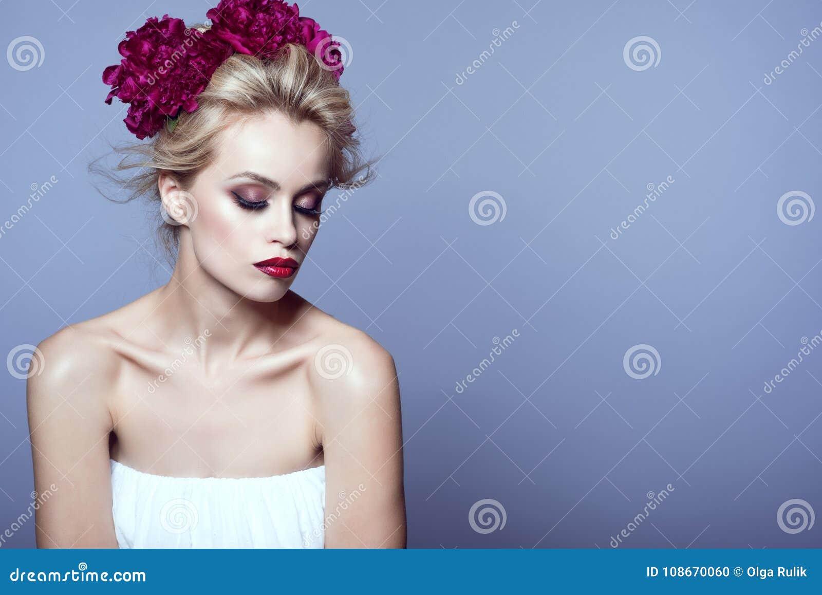 Le beau modèle blond avec des cheveux d updo soufflés par le vent et parfaits composent la guirlande principale sans bretelles bl