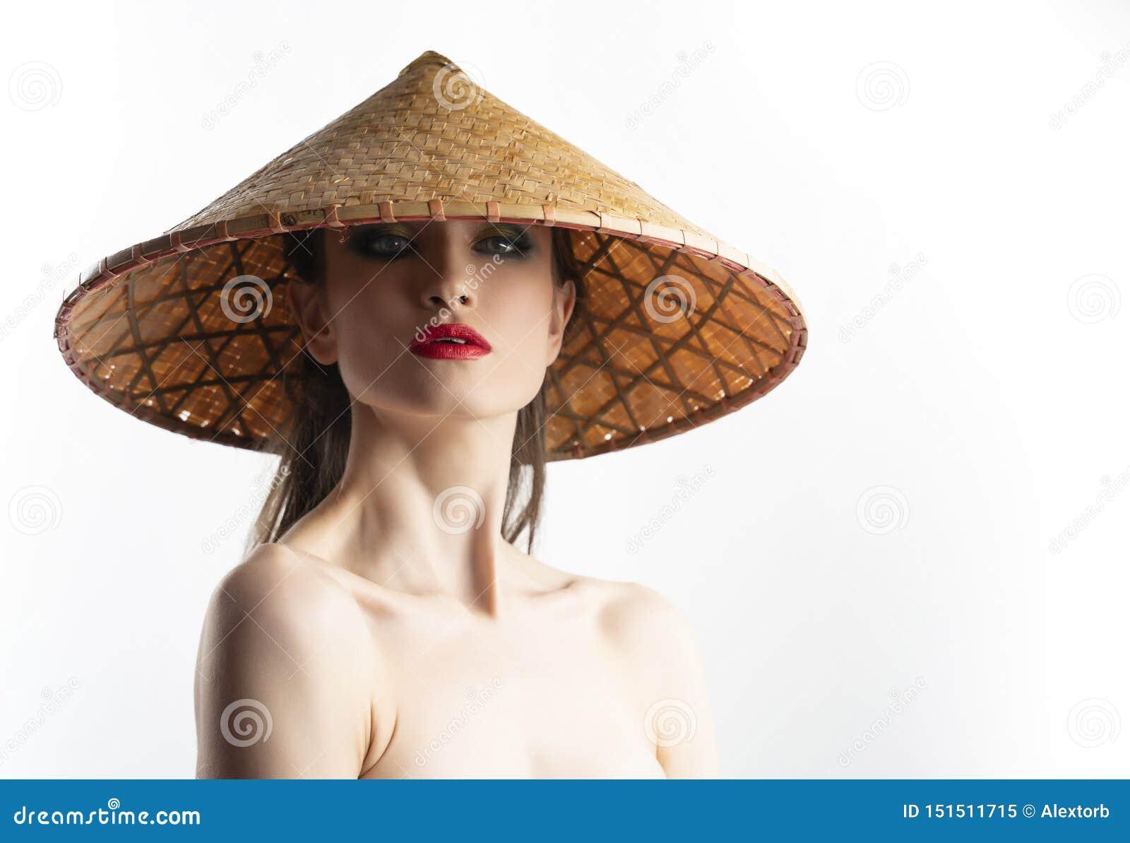 Le beau modèle de fille avec les lèvres rouges préparent et les épaules nues utilisant le chapeau vietnamien asiatique de cône fa