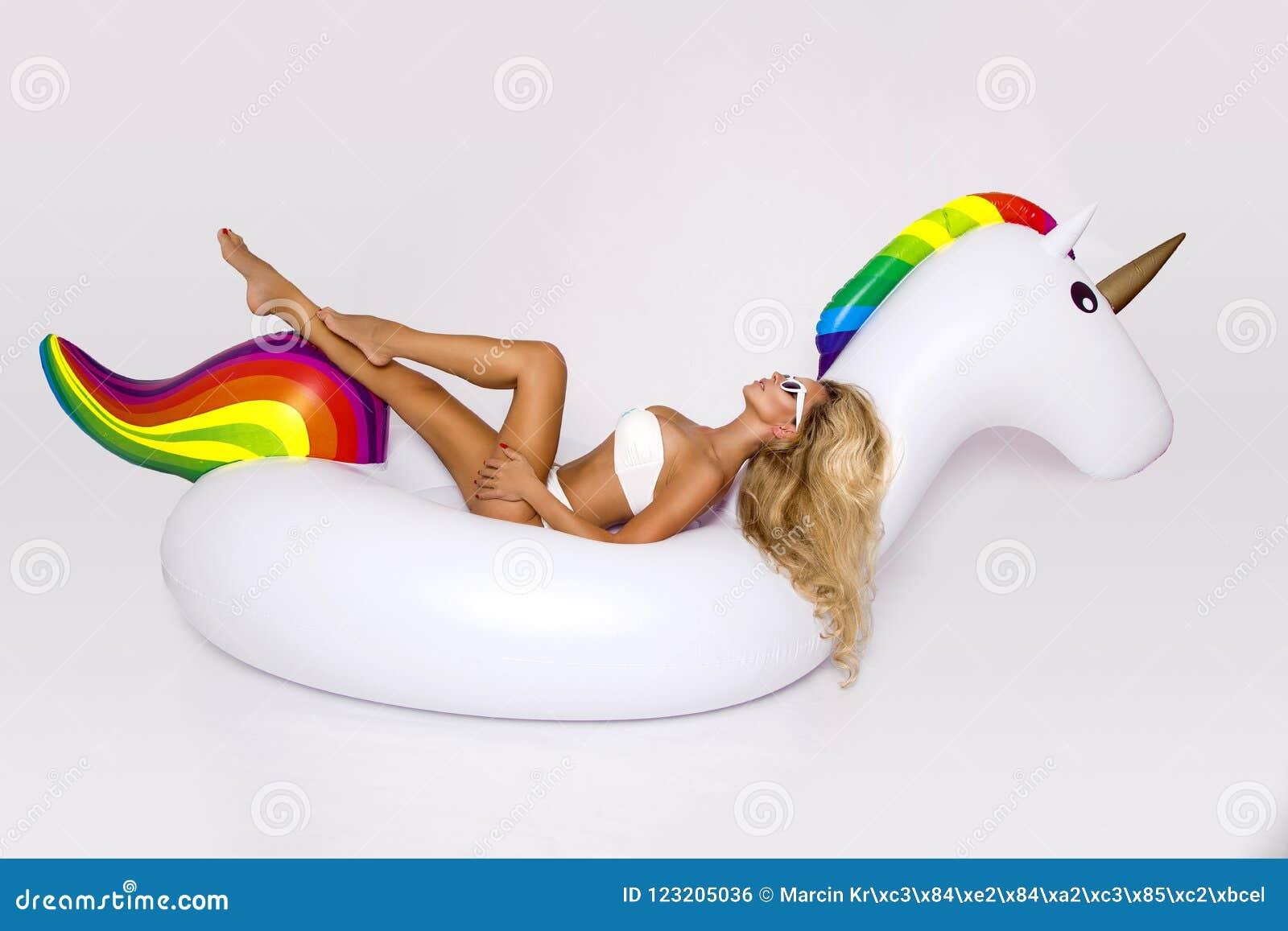 Le beau, sexy modèle blond dans un bikini élégant, se trouve sur une licorne blanche Frappez l été