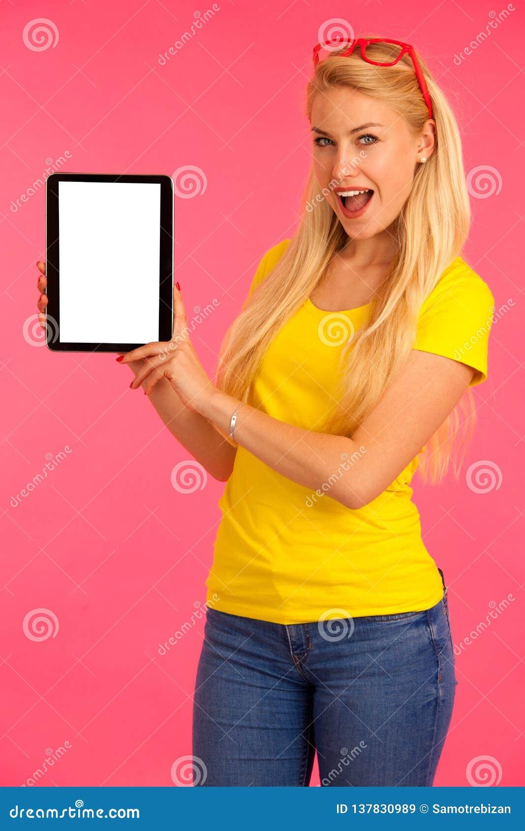 Le beau T-shirt de jaune de péché de jeune femme tient le comprimé et surfe l Internet au-dessus du fond rose