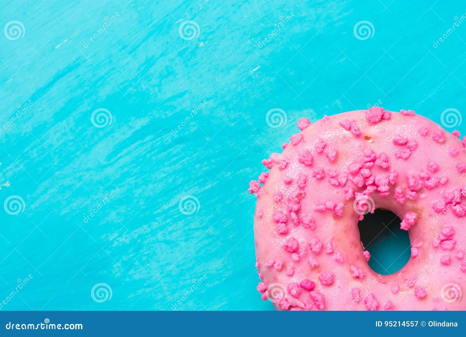 Le beignet vitré de rose avec du sucre arrose dans le bon coin inférieur sur le fond bleu-clair, copyspace, calibre, anniversaire