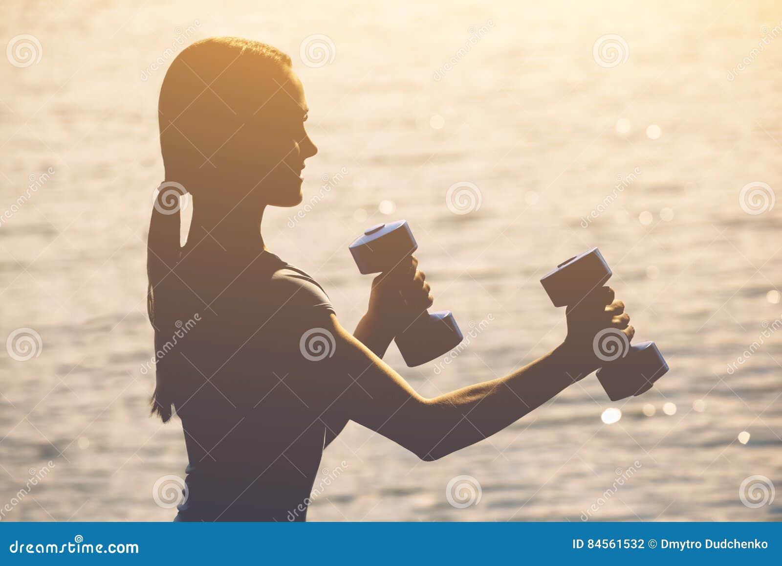 Le bel athlète impliqué dans les sports sur la rue conduit la formation avec des haltères dans des ses mains