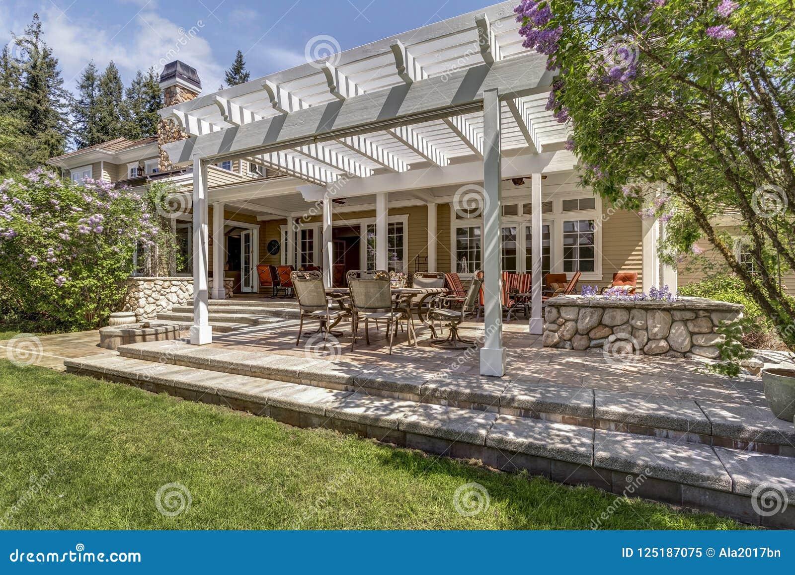 Le bel espace extérieur de patio de plate-forme avec la pergola dinante blanche
