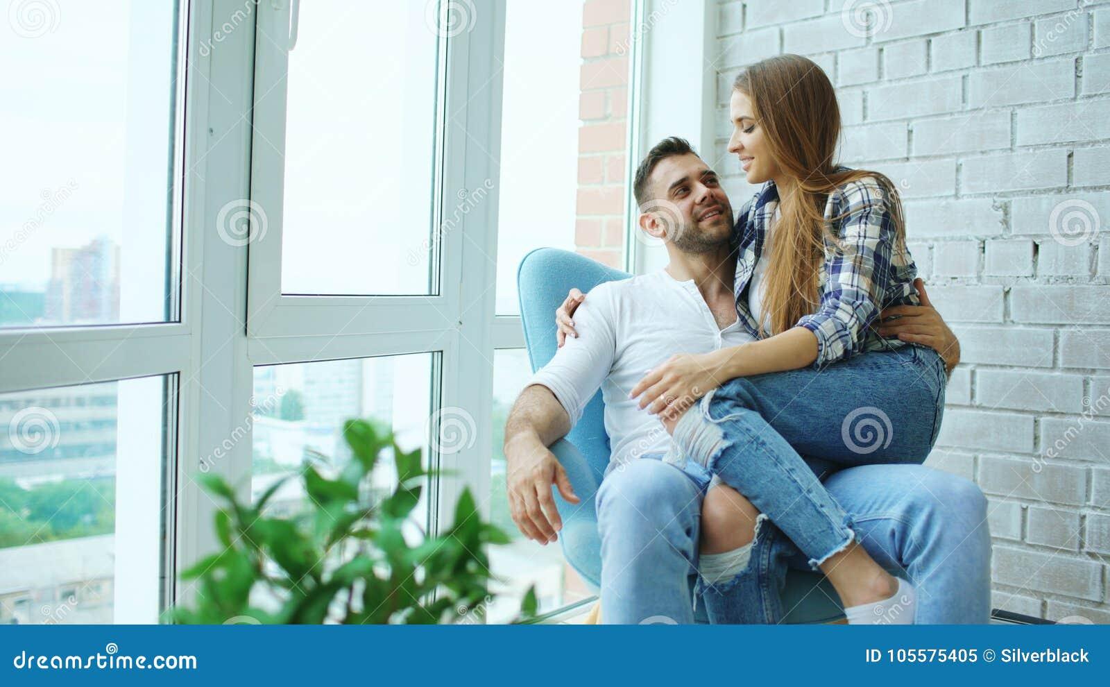 Le belle giovani coppie si rilassano la seduta sulla sedia e godere della vista dal balcone di nuovo appartamento del sottotetto
