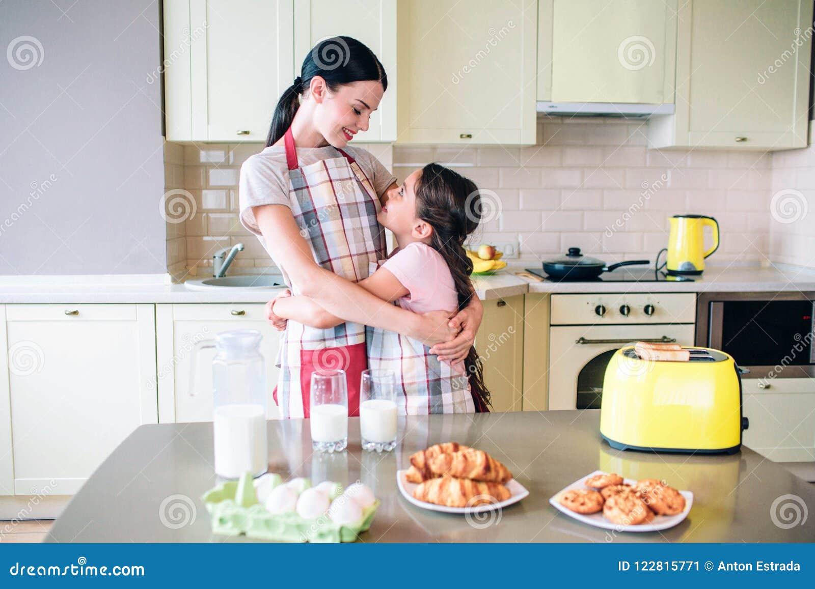 Le belle ragazze stanno esaminando reciprocamente e sorridere Abbracciano Le ragazze stanno stando vicino alla tavola con l alime