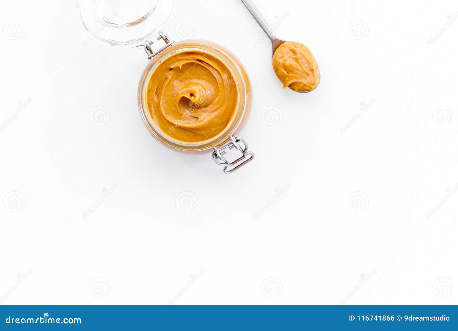 Le beurre d écrou, le beurre d arachide dans le pot en verre et la cuillère avec du beurre sur la vue supérieure de fond blanc co