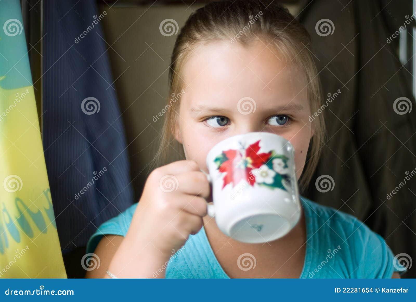 Le bevande della ragazza da una tazza