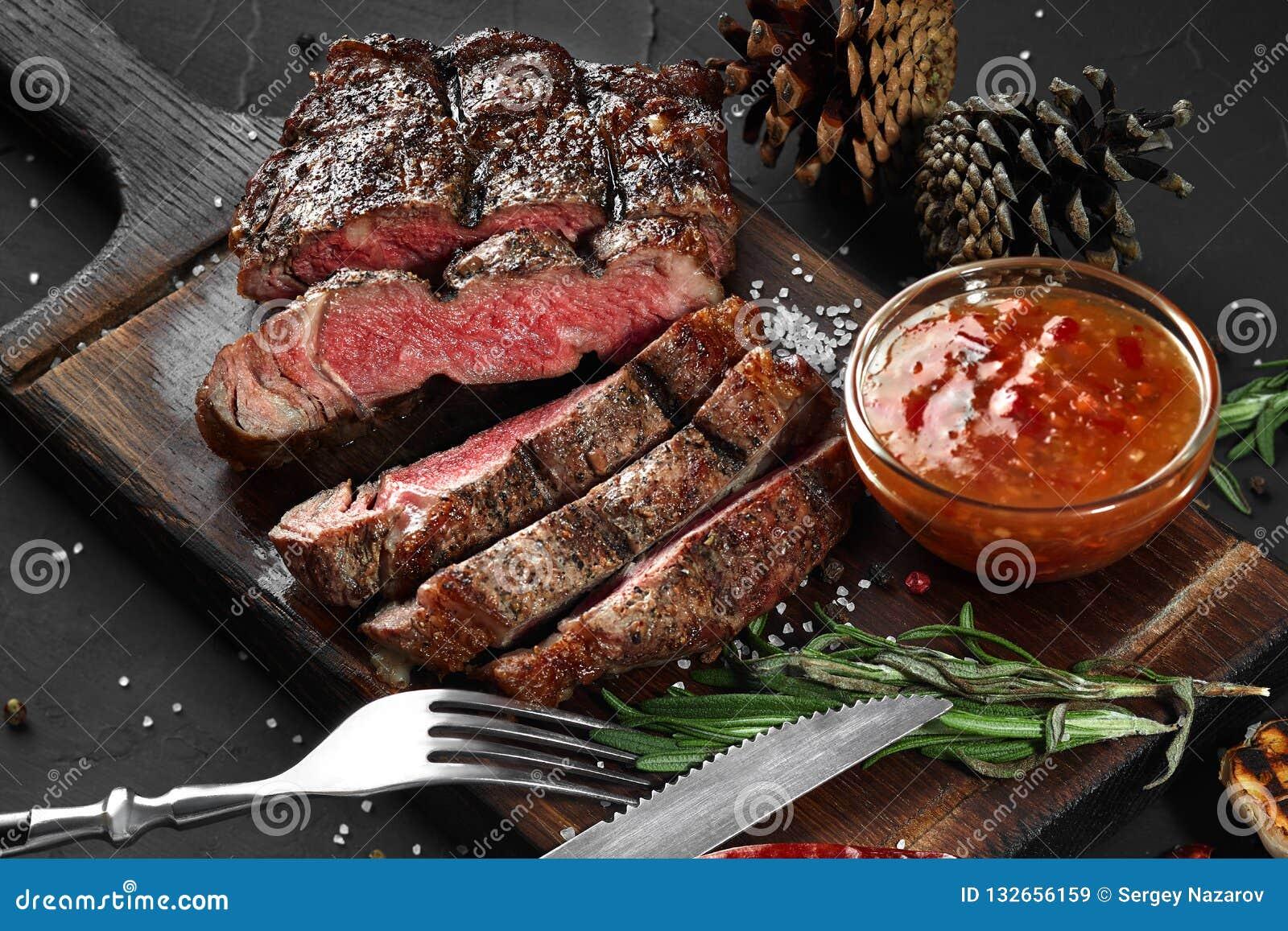 Le bifteck de boeuf rare moyen grillé coupé en tranches a servi sur le barbecue de conseil en bois, filet de boeuf de viande de B