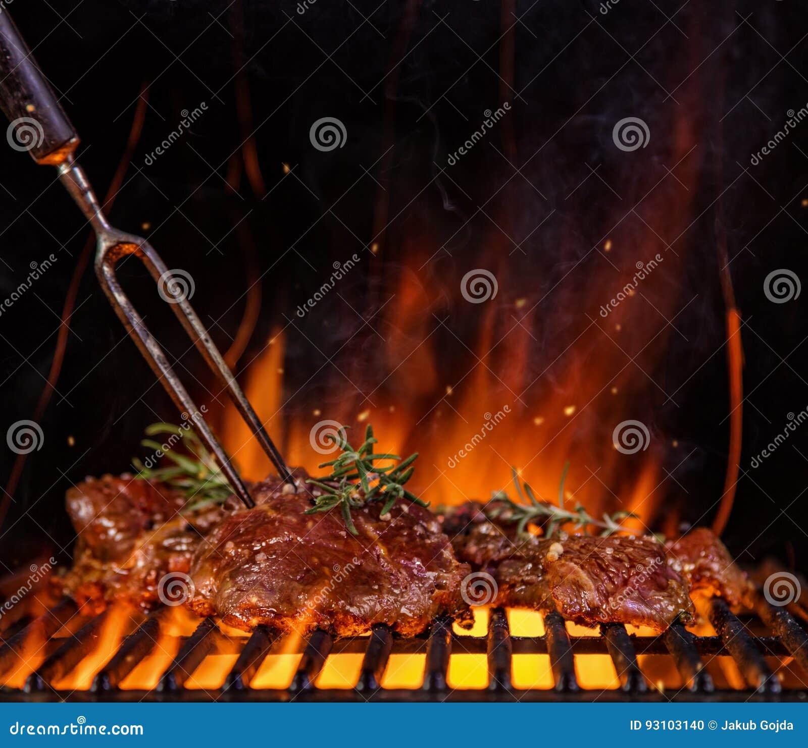 Le bistecche di manzo sulla griglia grattano, fiamme su fondo