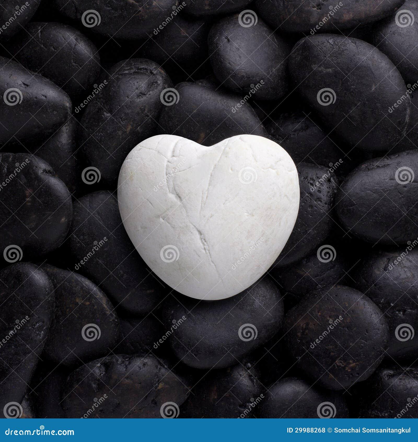Roche blanche, pierre dans la forme de coeur sur le caillou noir