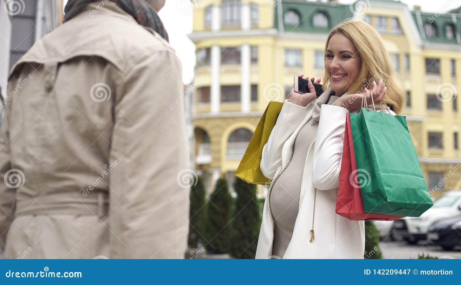 Le blivande modern som visar shoppingpåsar till vännen, barnsbördköp, försäljning