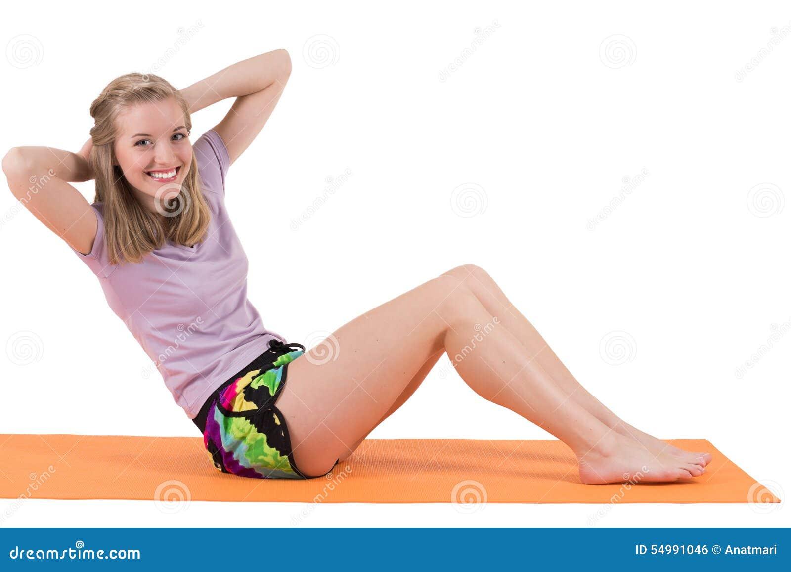 Le blonda muskler för kvinnautbildningsmage på ett mattt