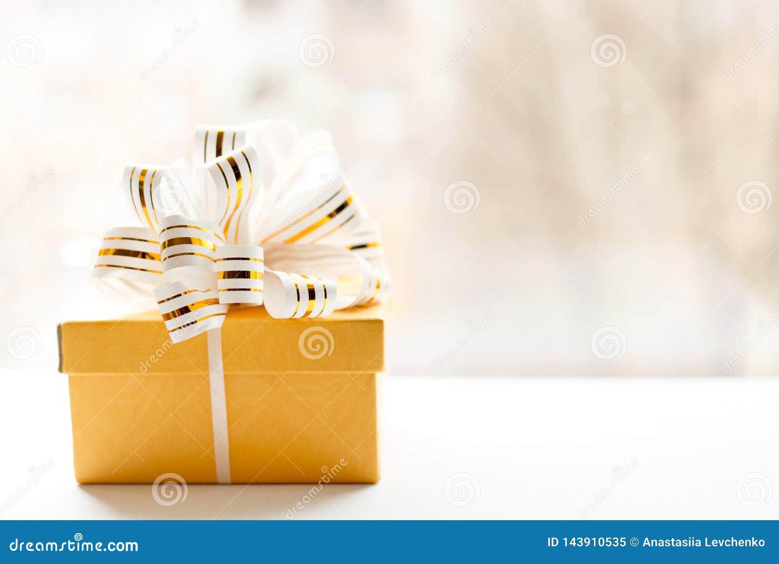 Le boîte-cadeau jaune enveloppé en blanc et or a barré le ruban sur le fond clair Note vide attachée plus de Copiez l espace Plac