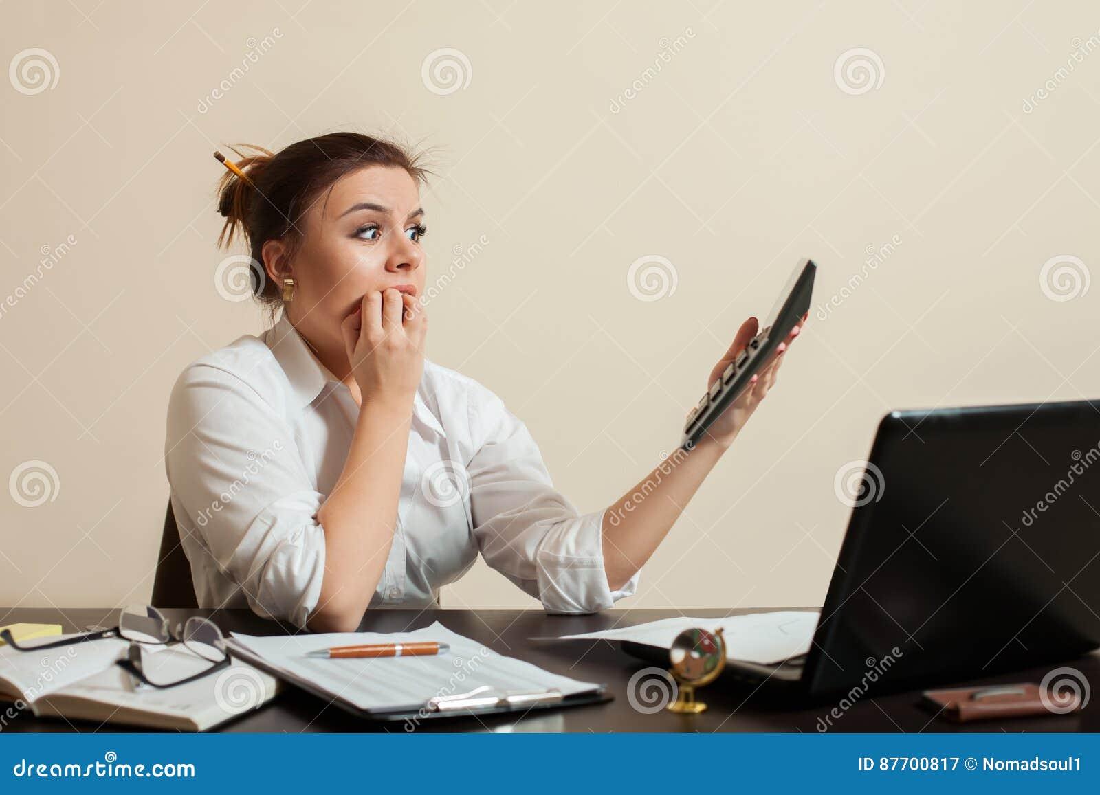 Le bookkeper femelle effrayé regarde le bilan
