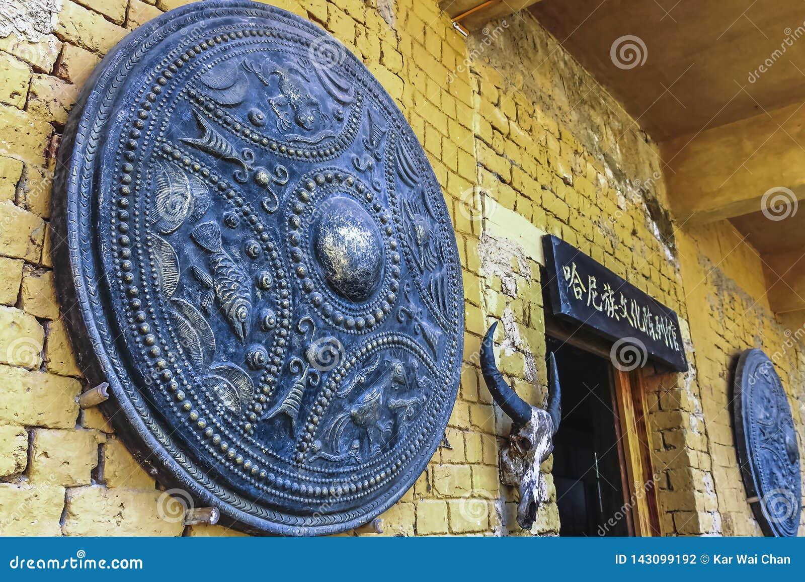 Le bouclier et la tête en bronze géants de chèvres décore la façade de la maison dans Yuanyang
