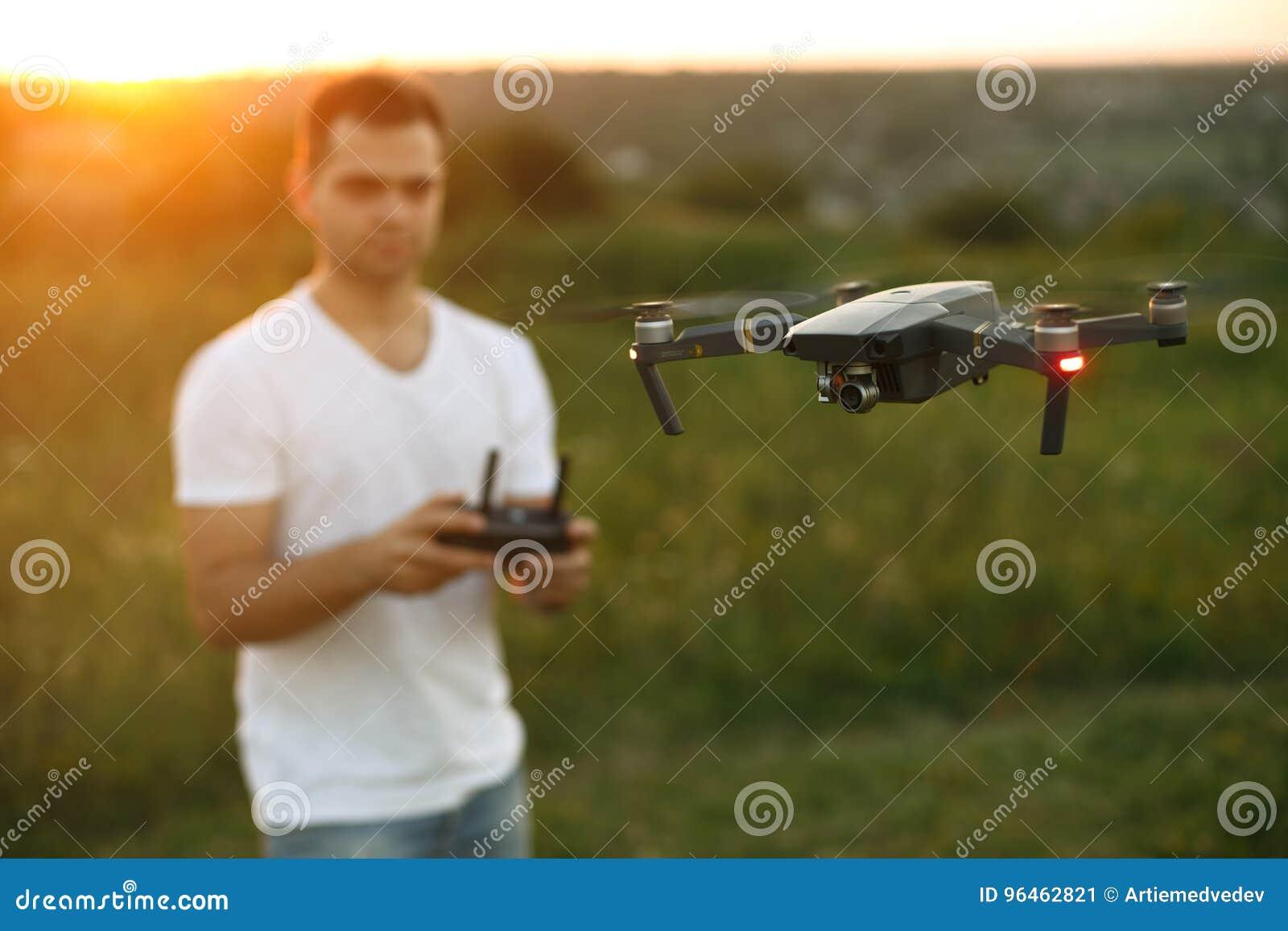 Le bourdon plane devant l homme avec le contrôleur à distance dans des ses mains Quadcopter vole près du pilote Type prenant les