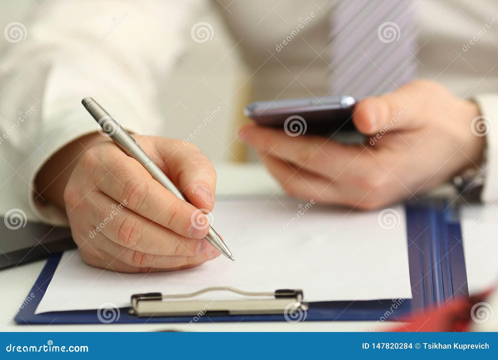 Le bras masculin dans le costume et le lien tiennent le stylo argent?
