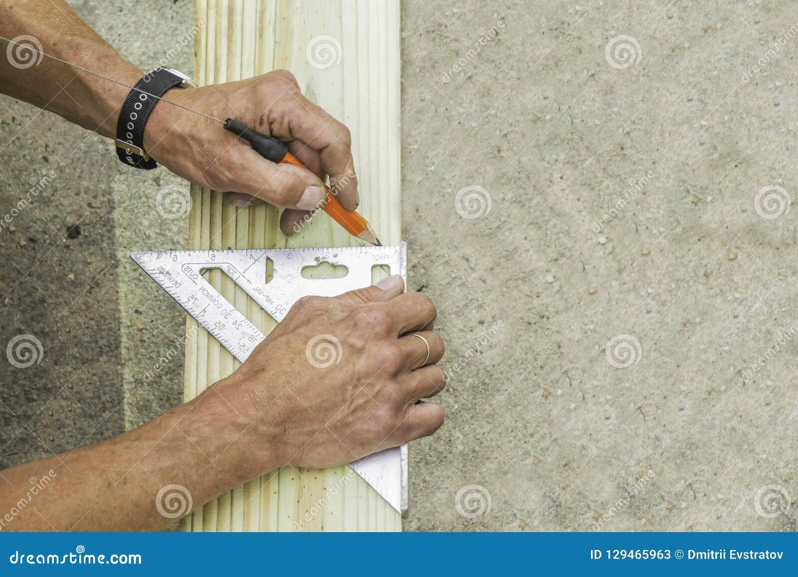 Le bricoleur marque le conseil avec un crayon et une place