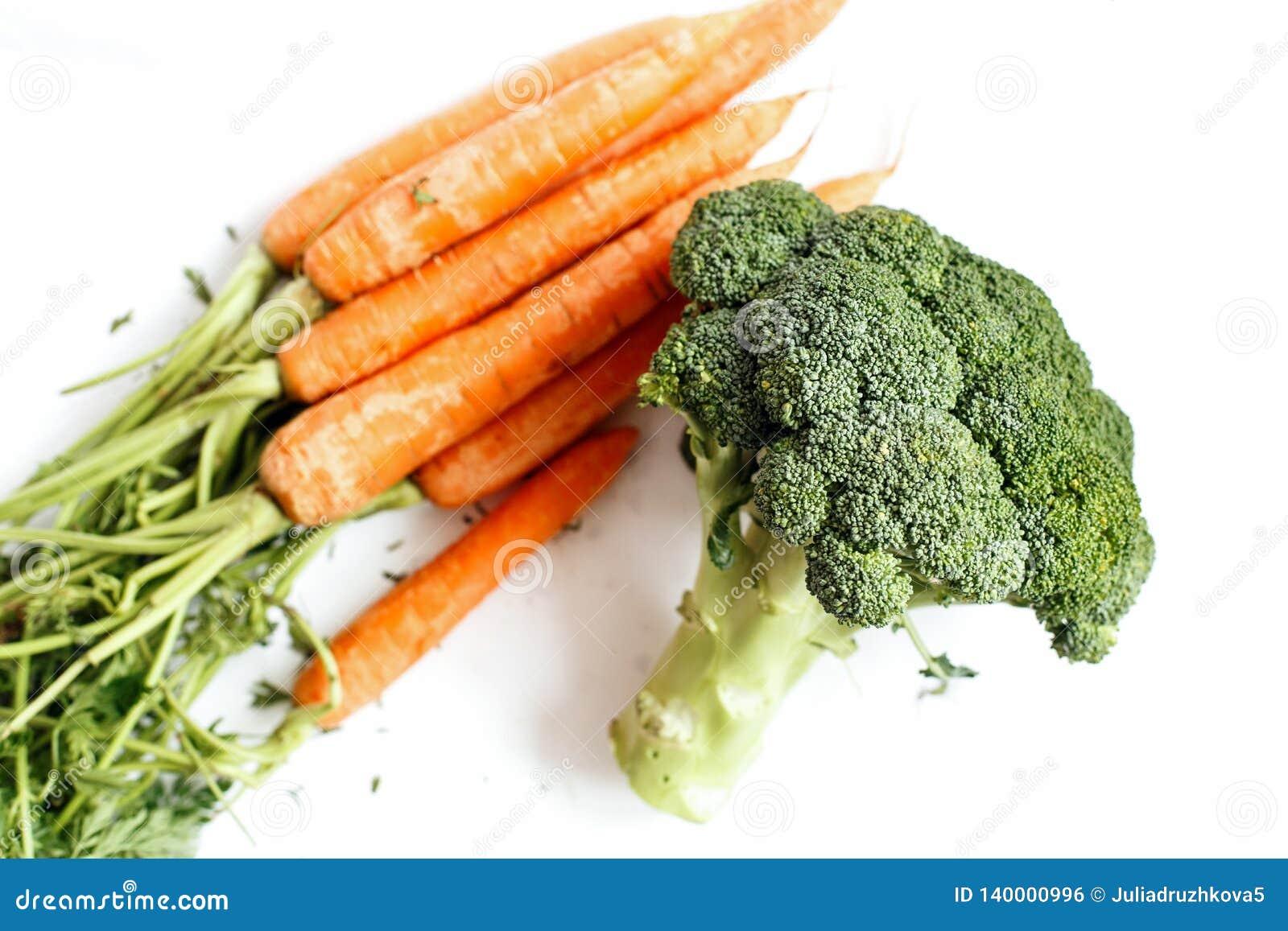 Le brocoli et quelques carottes sont sur un fond blanc Toujours durée comestible