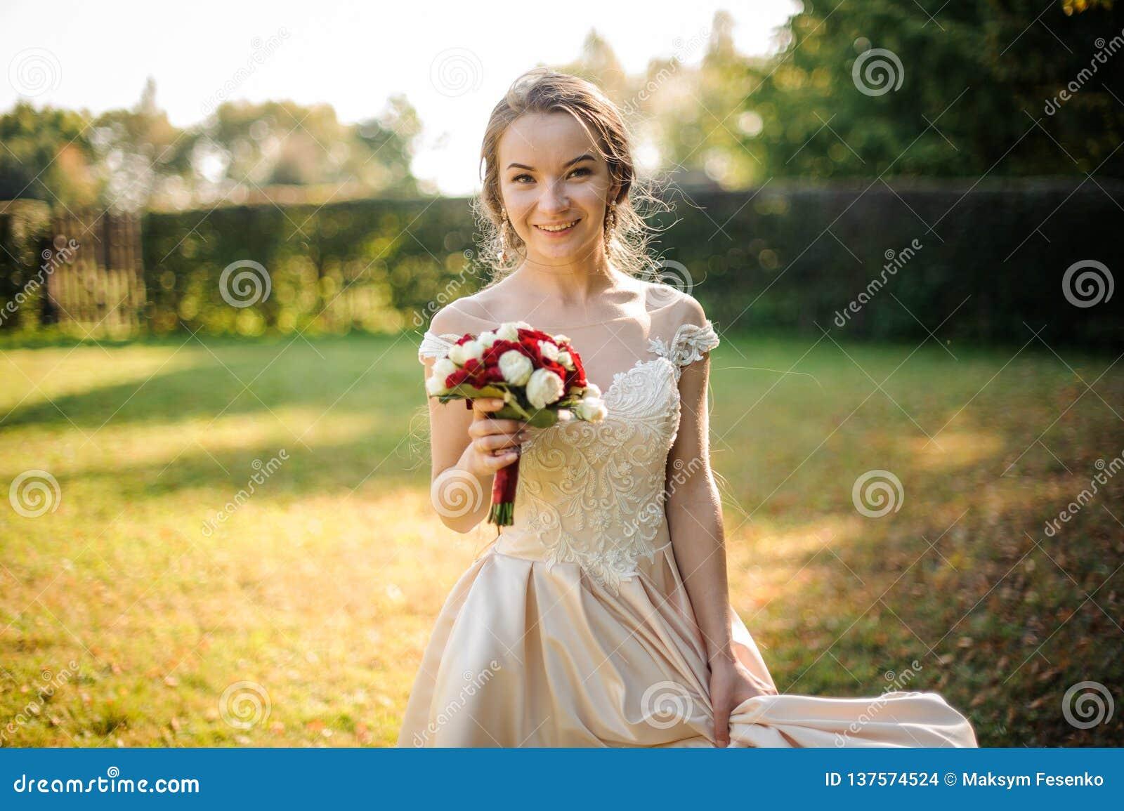 Le bruden i en vit bröllopsklänning som rymmer en beauriful bukett för röda rosor