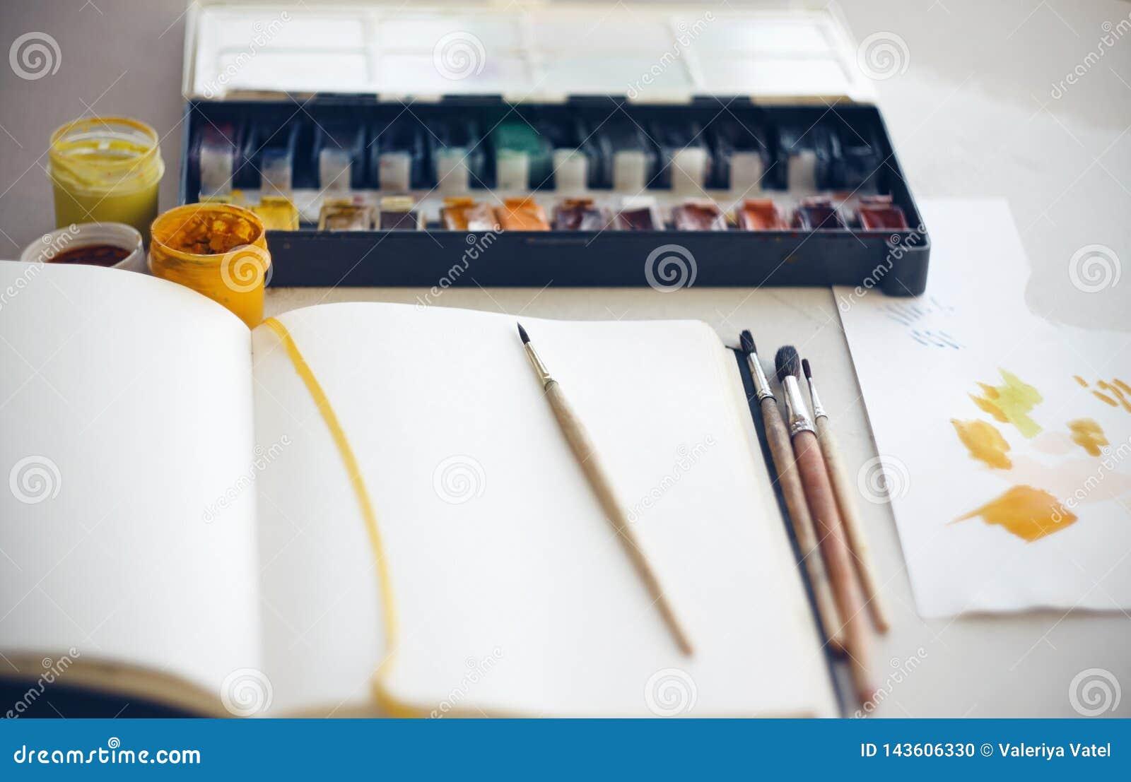 Le bureau de l artiste sur quels carnet à dessins, brosses, aquarelle et peintures de gouache