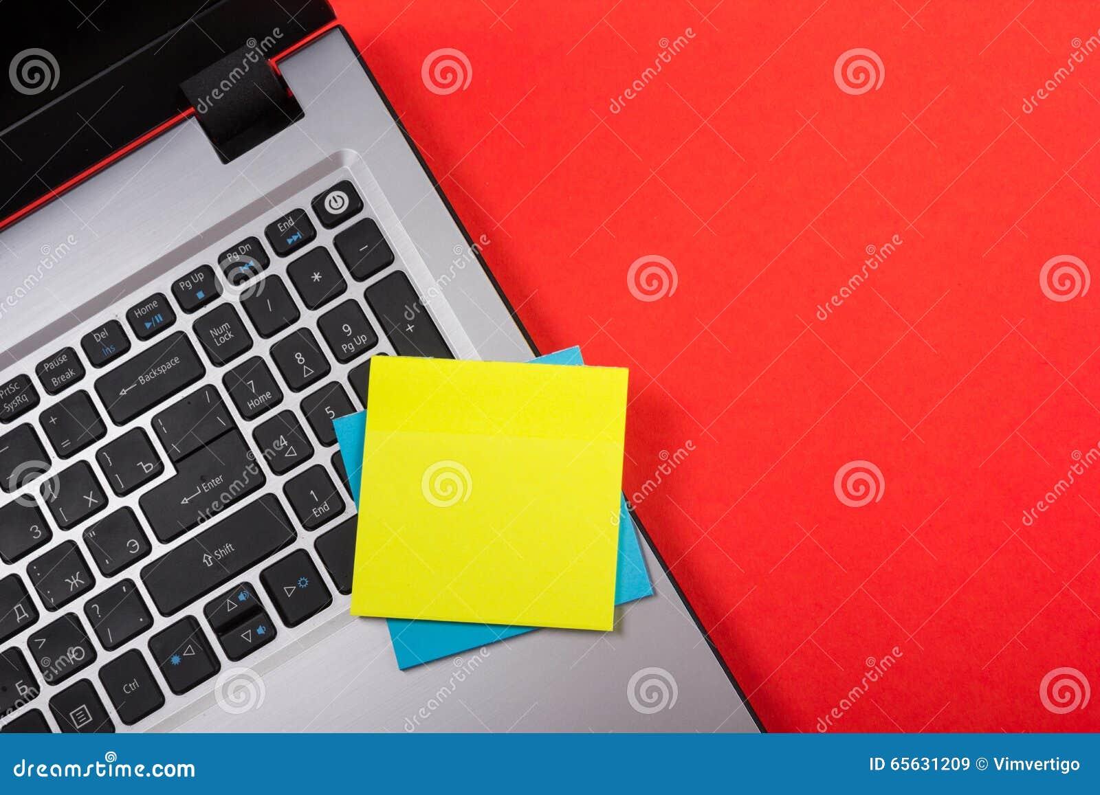 Le bureau de table de bureau avec l ensemble d approvisionnements colorés, bloc-notes vide blanc, tasse, stylo, PC, a chiffonné l