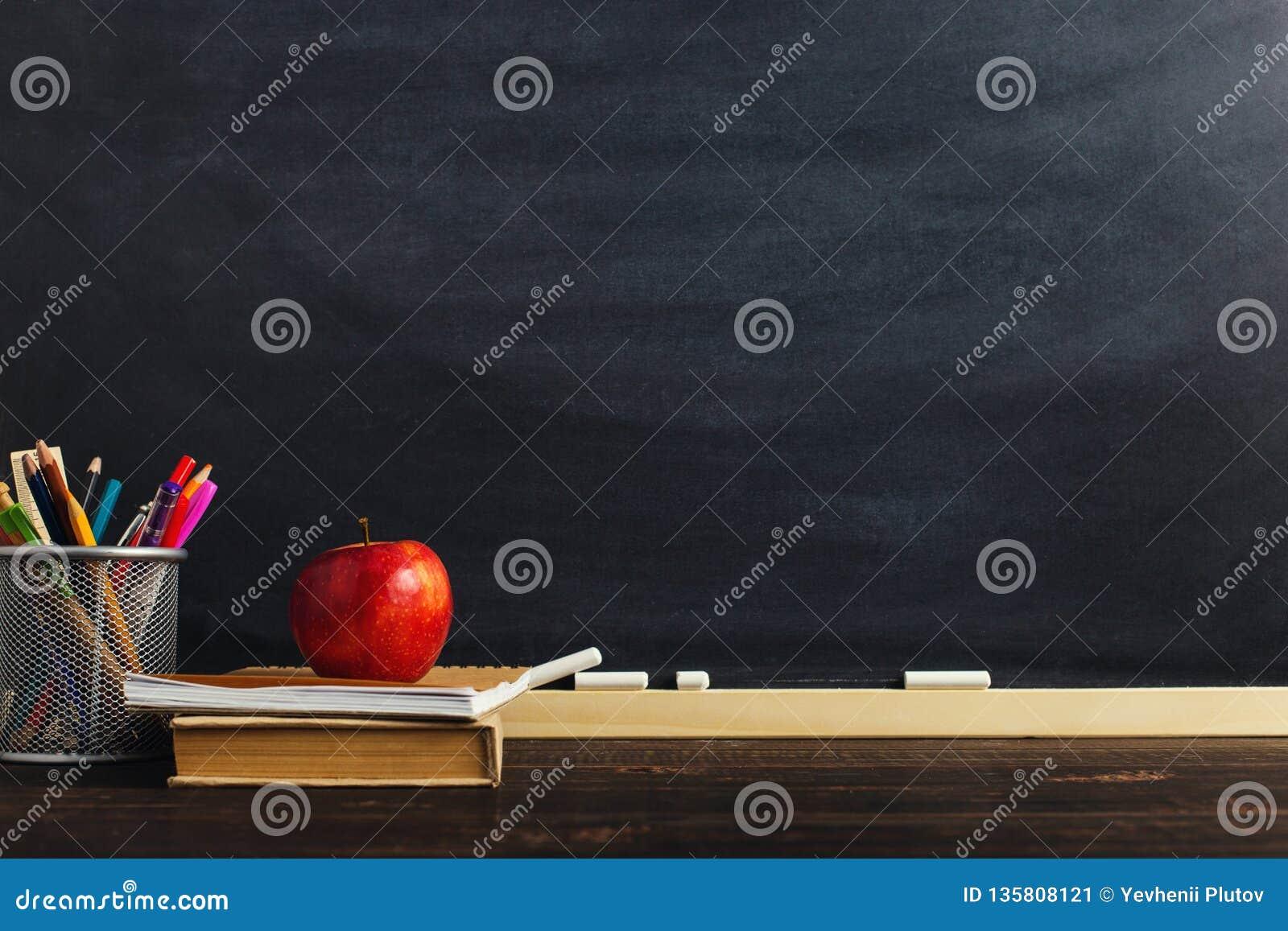 Le bureau du professeur avec des matériaux d écriture, un livre et une pomme, un blanc pour le texte ou un fond pour un thème d é