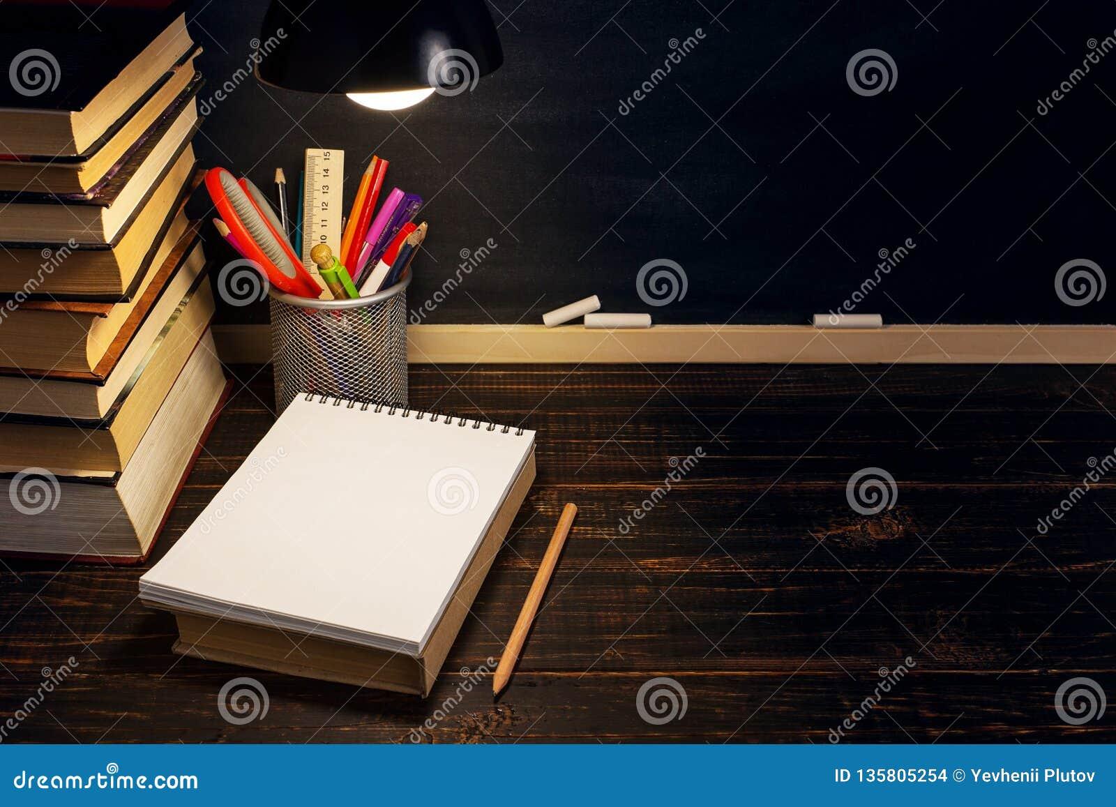 Le bureau ou un travailleur du professeur, sur lesquels les matériaux d inscription se trouvent, livres, le soir sous la lampe Bl