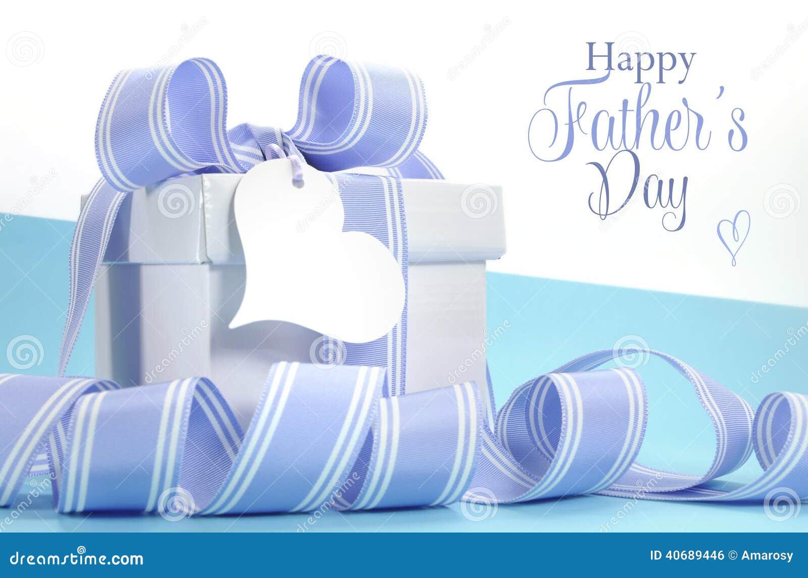 Le cadeau bleu de jour de pères avec le beau ruban de rayure et le coeur forment l étiquette de cadeau