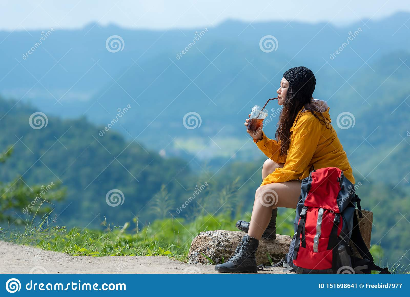 Le café se reposant et potable de femme asiatique de randonneur pour détendent et se reposent sur la montagne Sac à dos femelle e