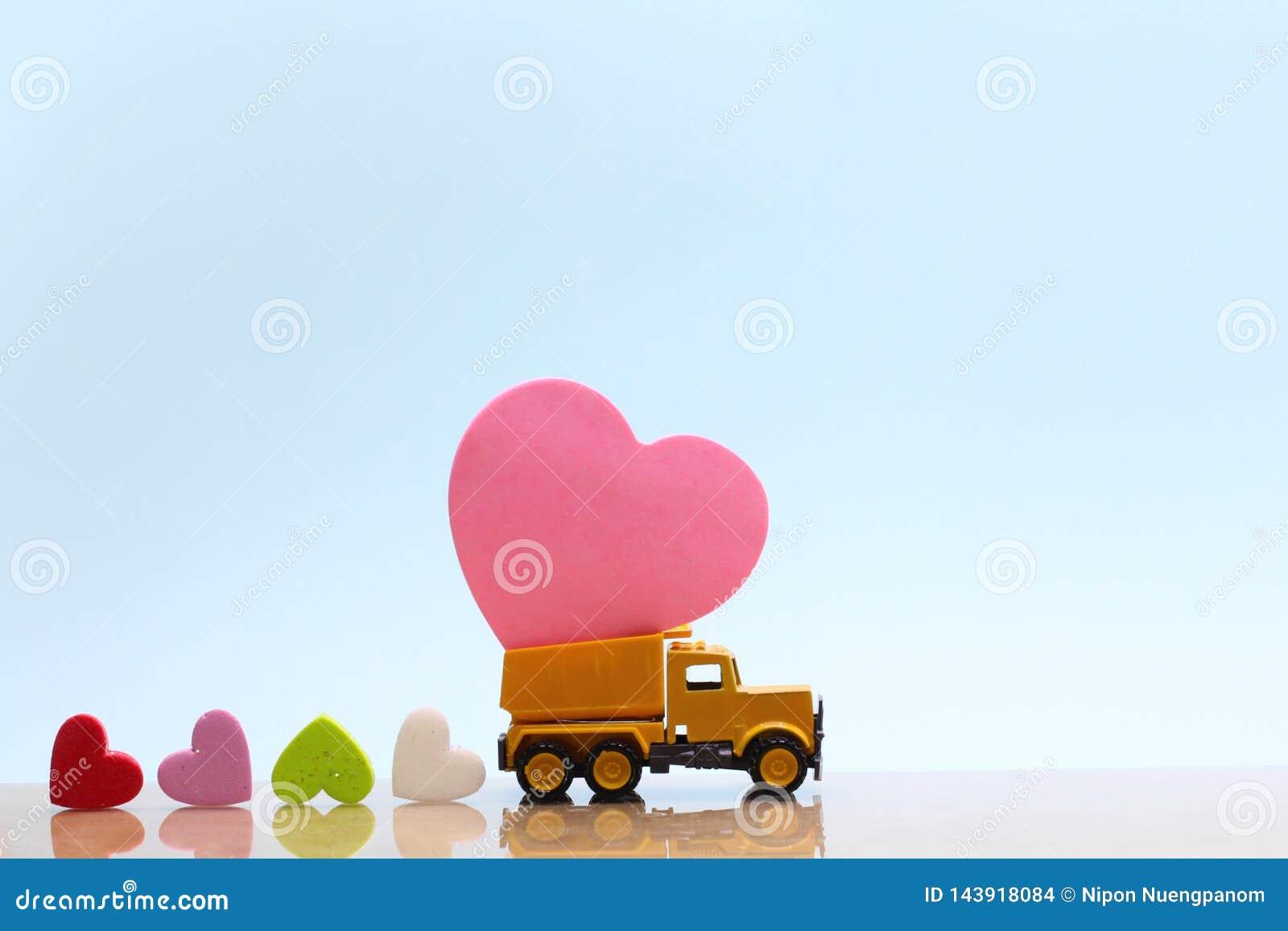 Le camion jaune de jouet continuent le coeur rose et beaucoup de coeurs colorés sur le fond bleu
