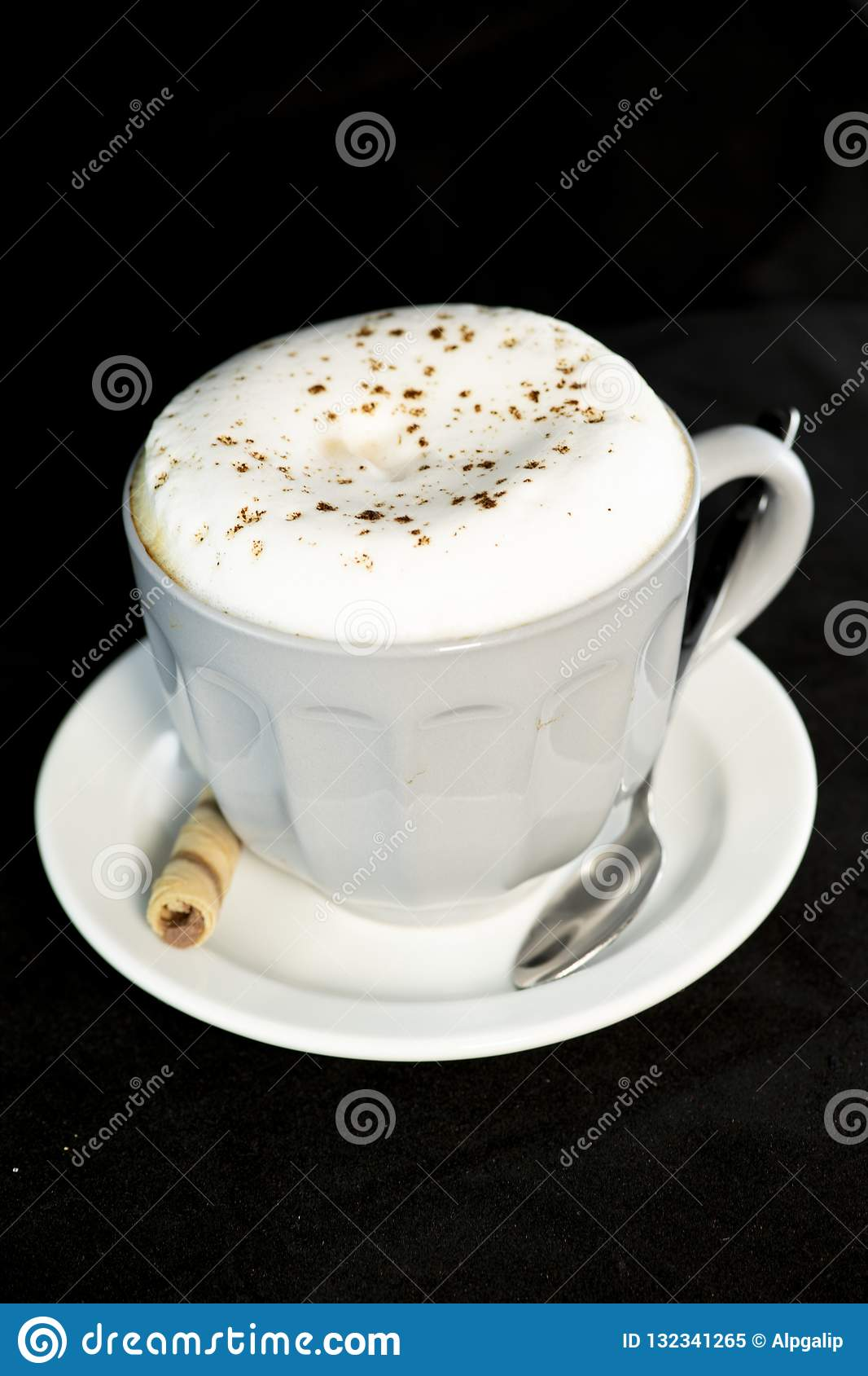 Le cappuccino délicieux a servi avec le petit pain de gaufrette de noisette de chocolat