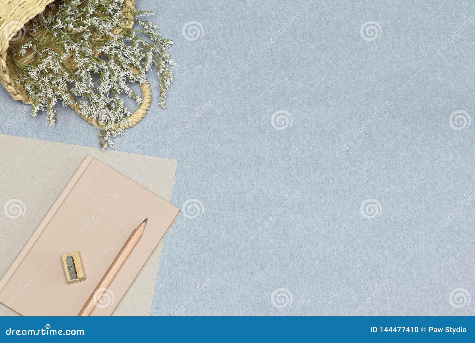 Le carnet rose, le crayon en bois et l aff?teuse, panier avec des fleurs sur le bureau bleu