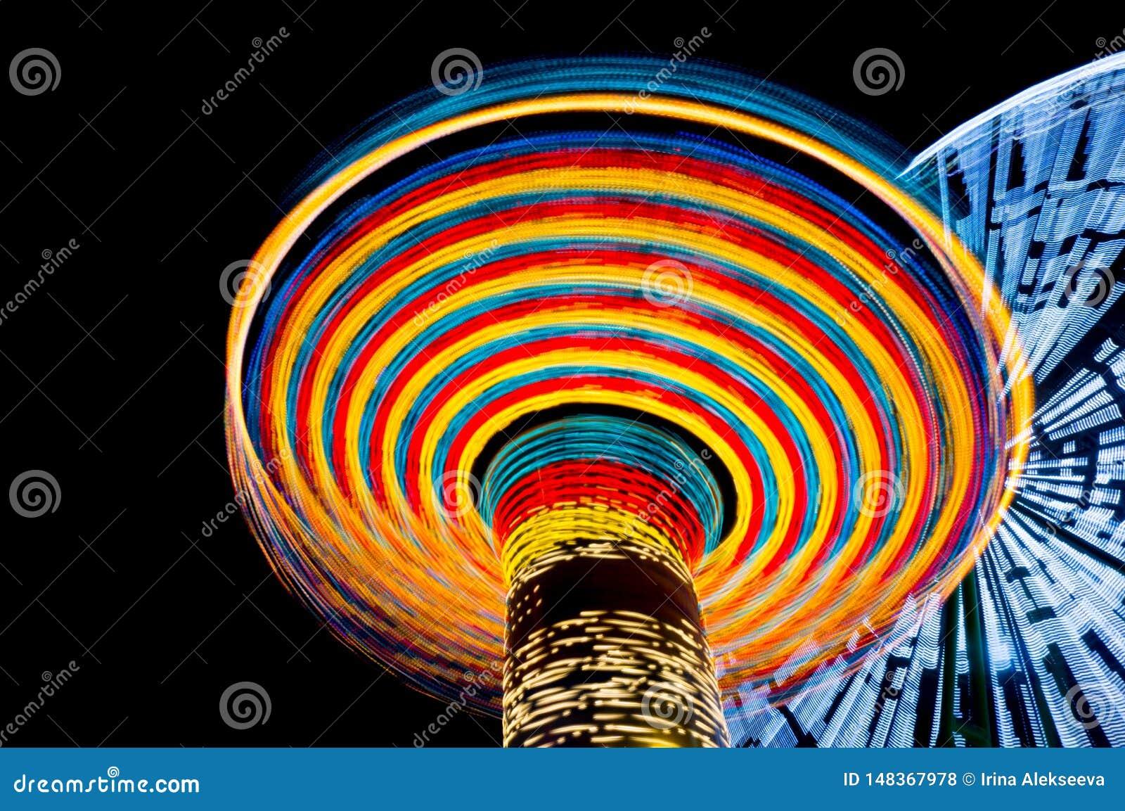 Le carrousel et les ferris roulent dedans un parc d attractions la nuit, longue exposition Concept de vitesse