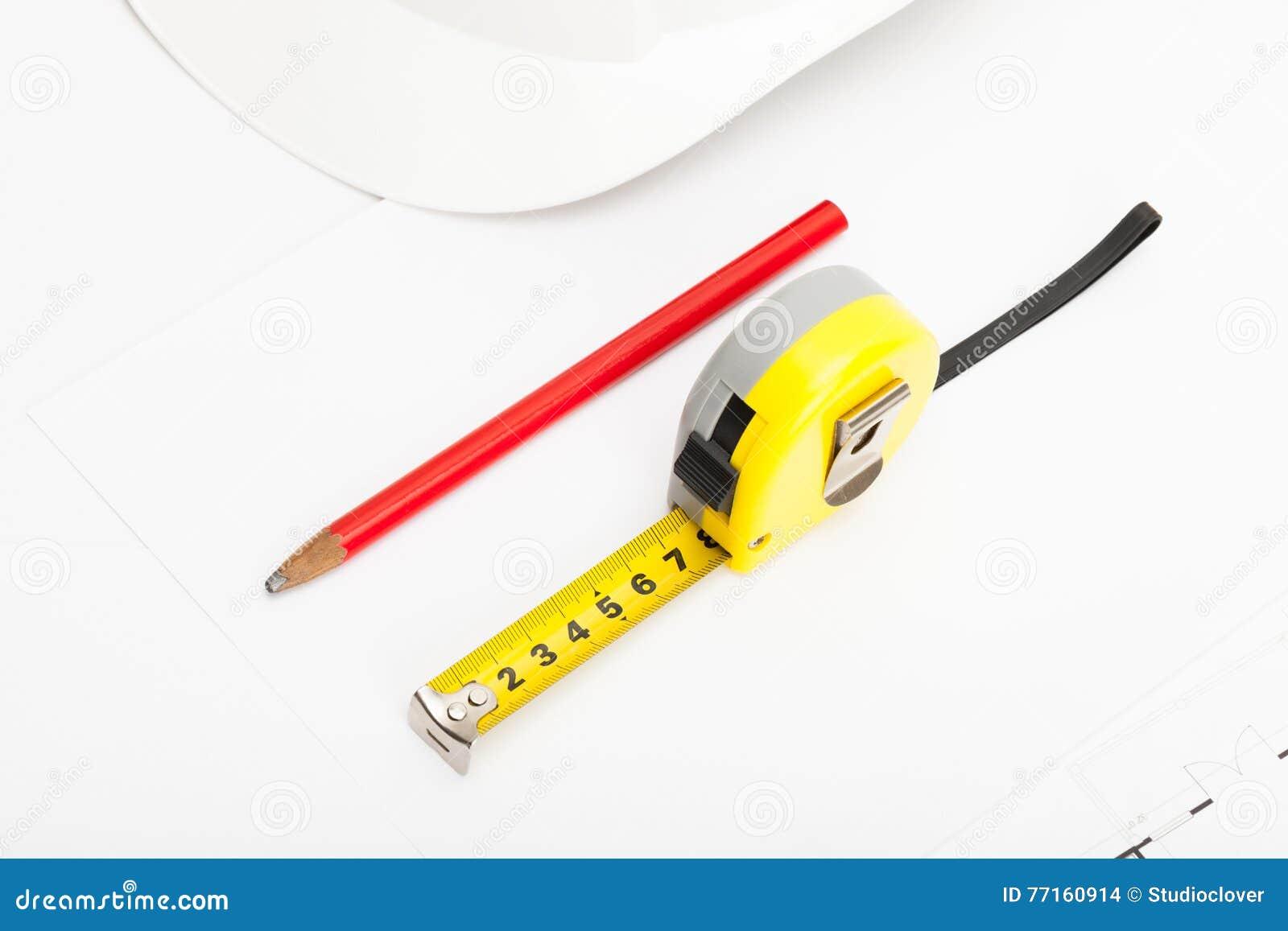 Le casque blanc de construction avec le crayon et la mesure attachent du ruban adhésif près de lui