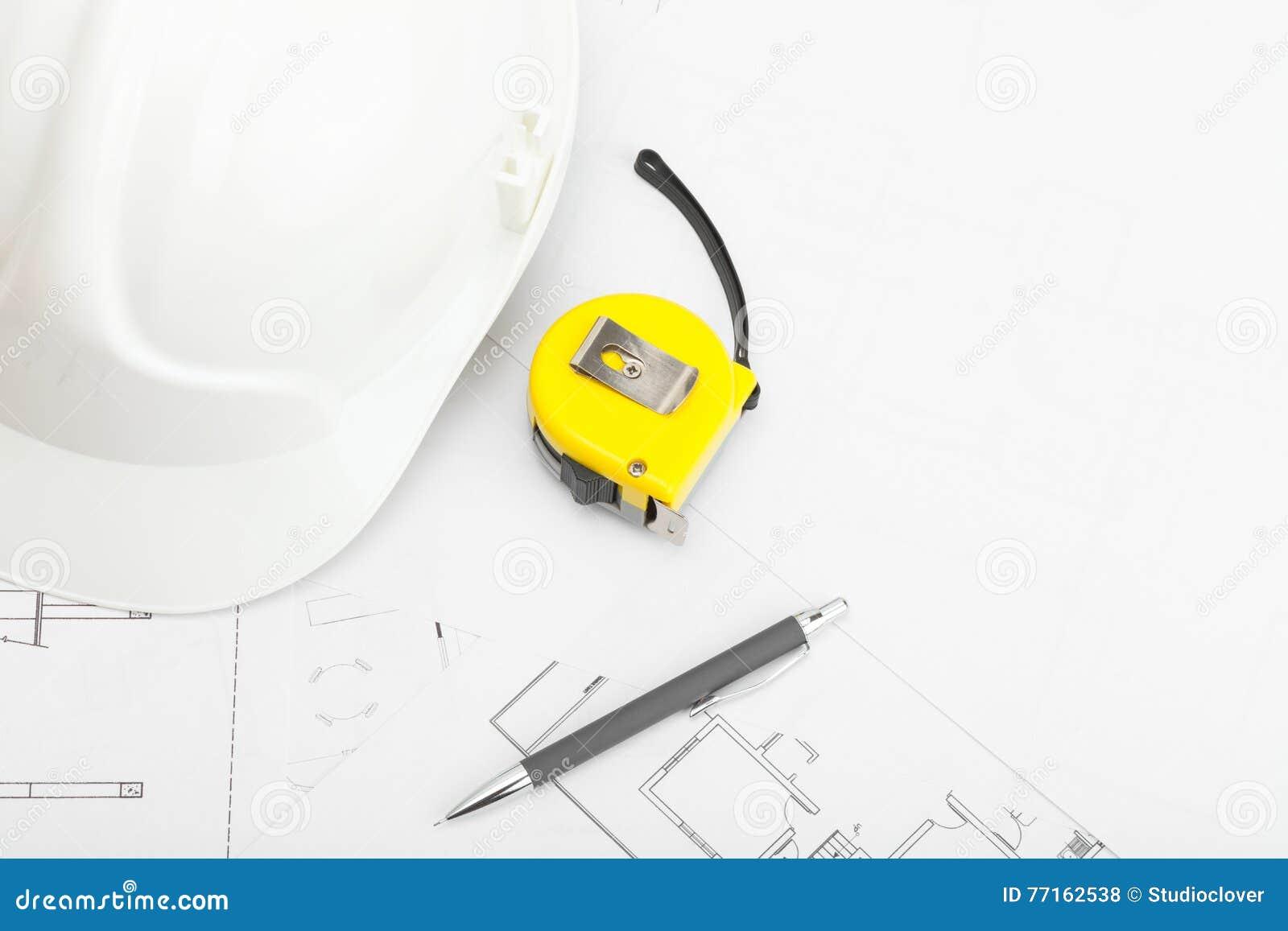 Le casque de construction avec le crayon et la mesure attachent du ruban adhésif près de lui