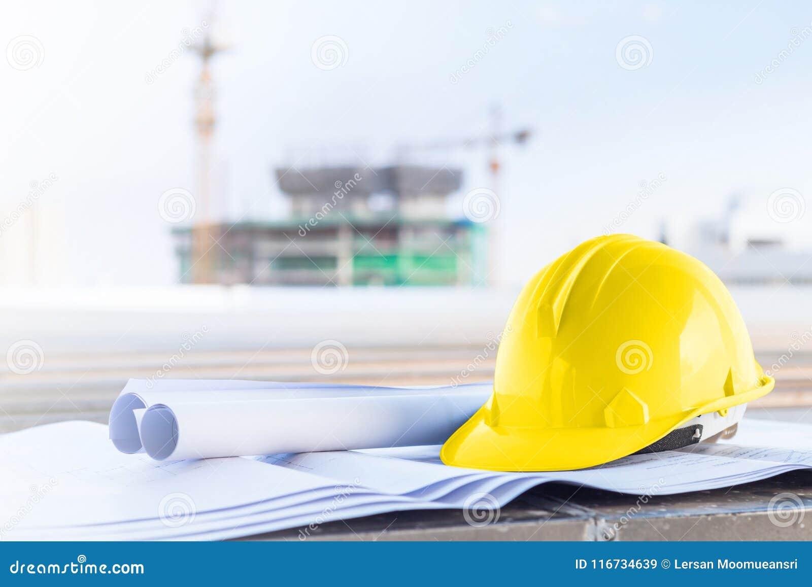 Le casque de sécurité jaune et le modèle au chantier de construction