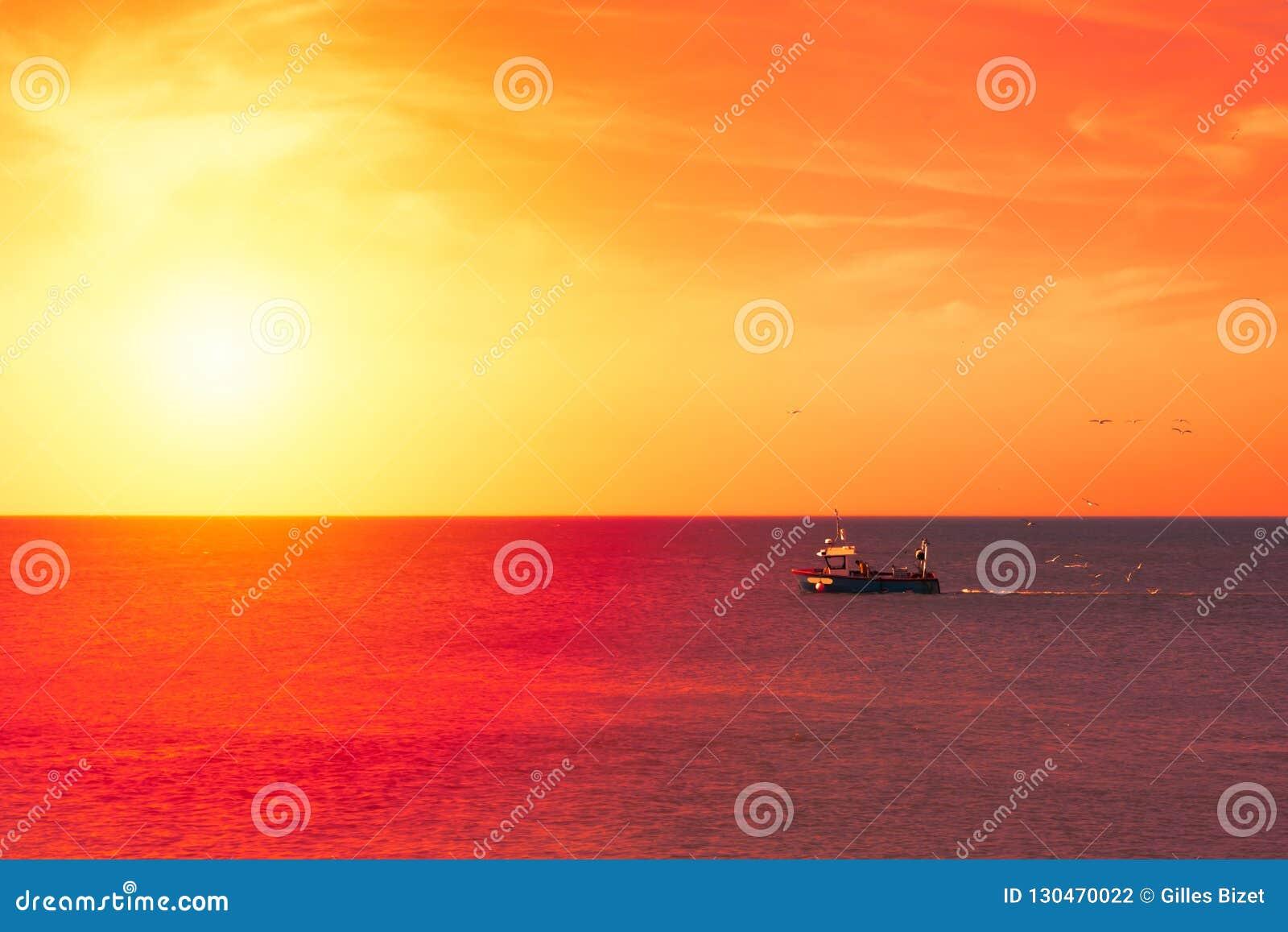 Le chalutier retourne pour mettre en communication au coucher du soleil