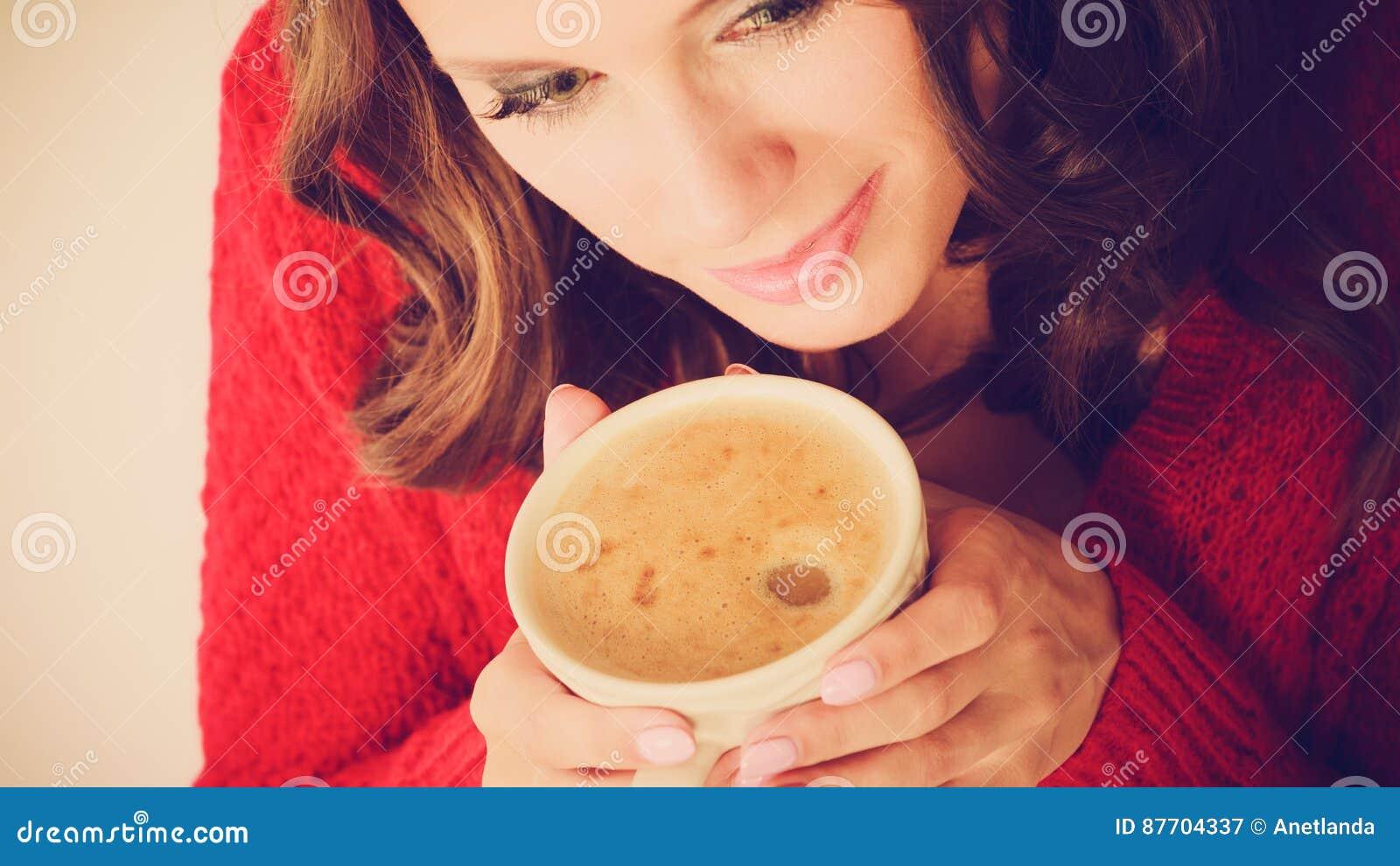 Le chandail rouge de fille tient la tasse avec du café