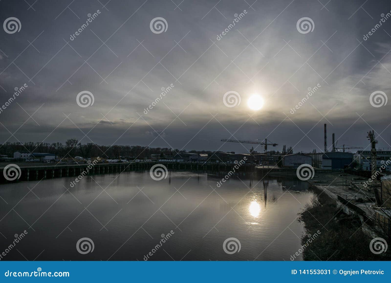 Le chantier naval sur la rivière assouvit pendant que le soleil descend lentement sur l horizon
