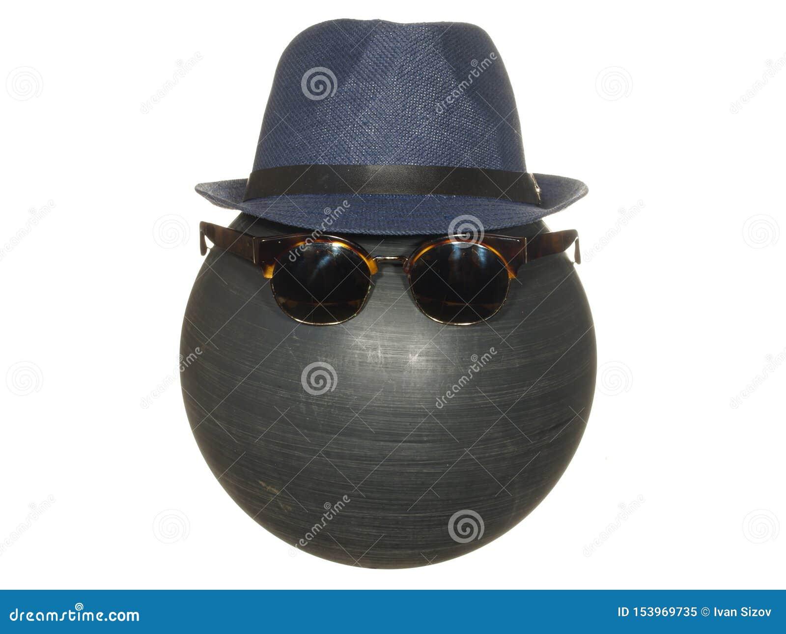 Le chapeau bleu et les lunettes foncées des hommes sur une boule en plastique noire d isolement sur le fond blanc