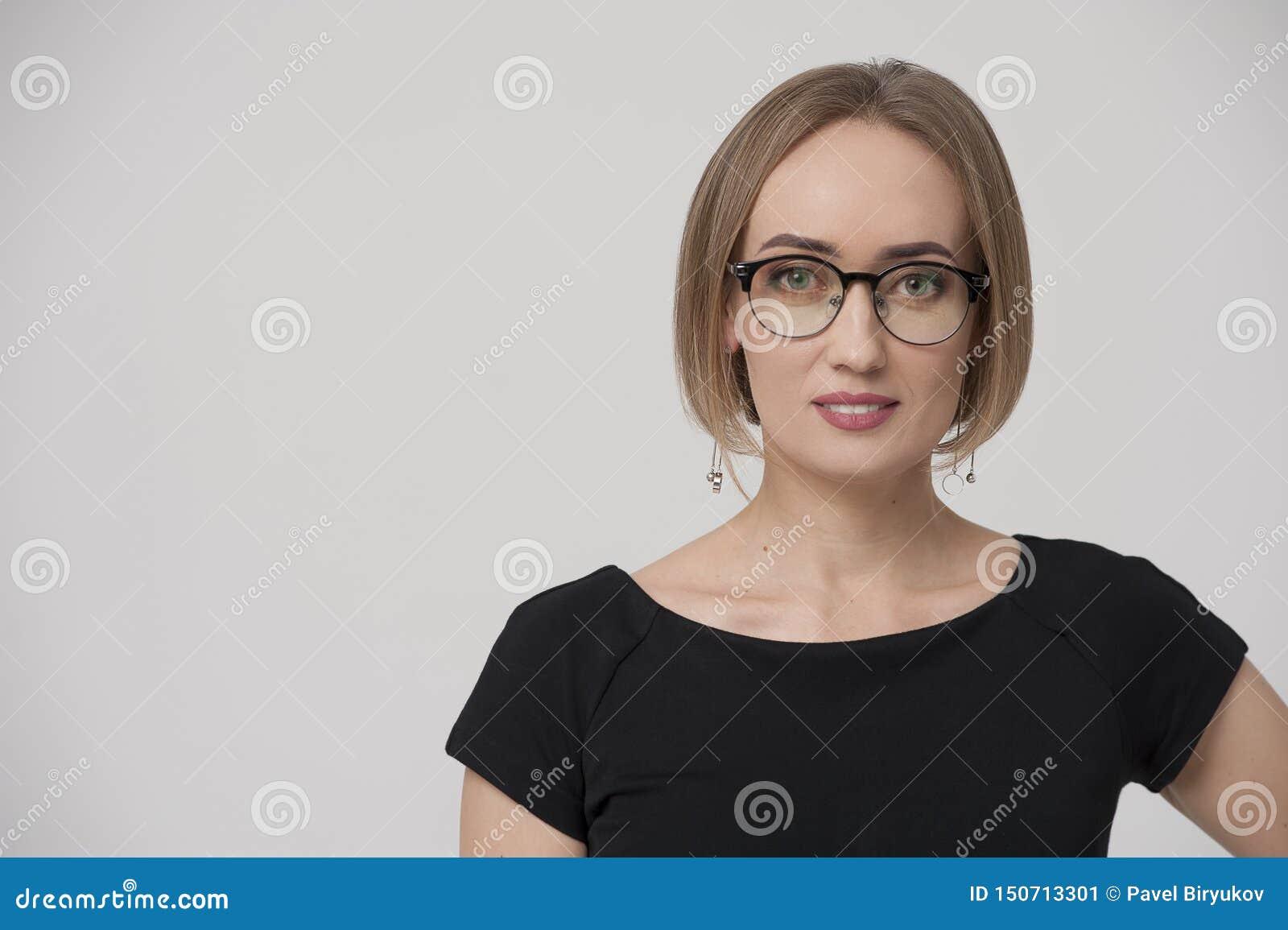 Le charma den unga affärskvinnan som bär den formella dräkten och stilfulla exponeringsglas