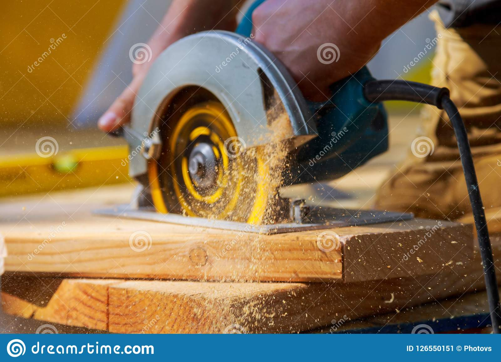 Le charpentier employant la circulaire a vu pour couper les conseils en bois avec des machines-outils de main