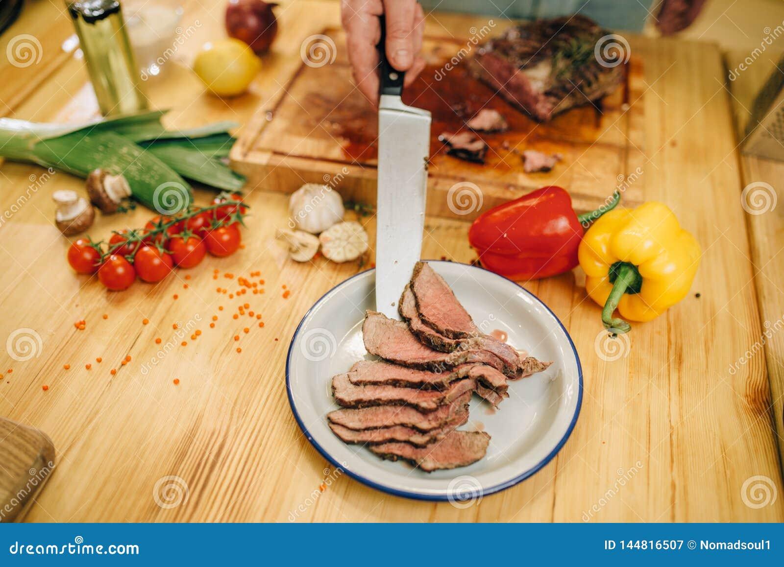 Le chef avec le couteau met la viande rôtie dans le plat