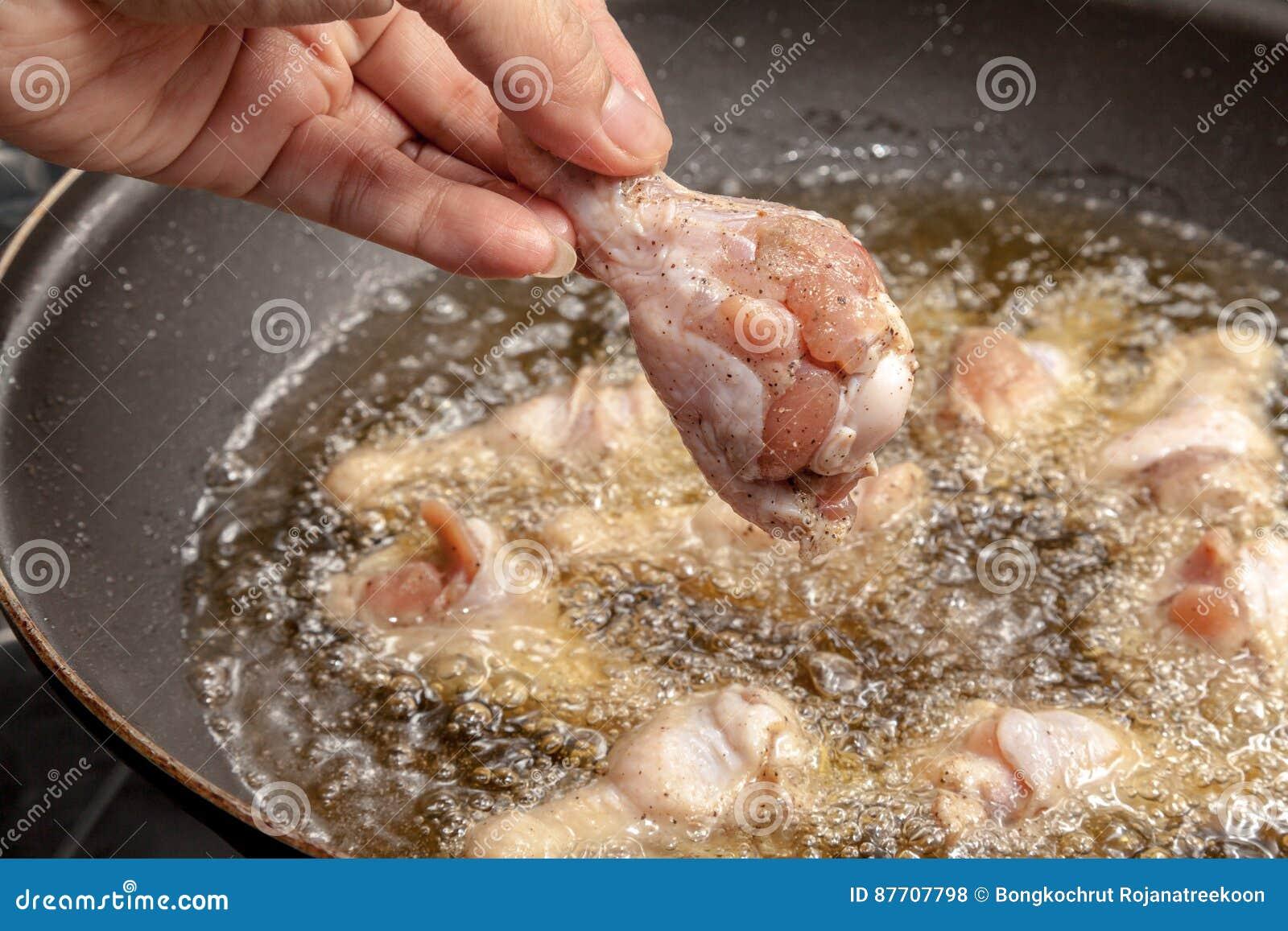 Le chef fait cuire des ailes de poulet frit dans la casserole