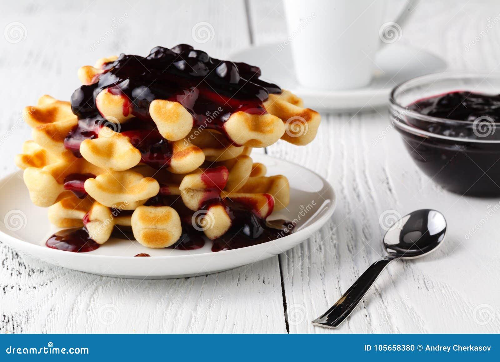 Le cialde belghe con creem e berrie si inceppano su fondo di legno bianco