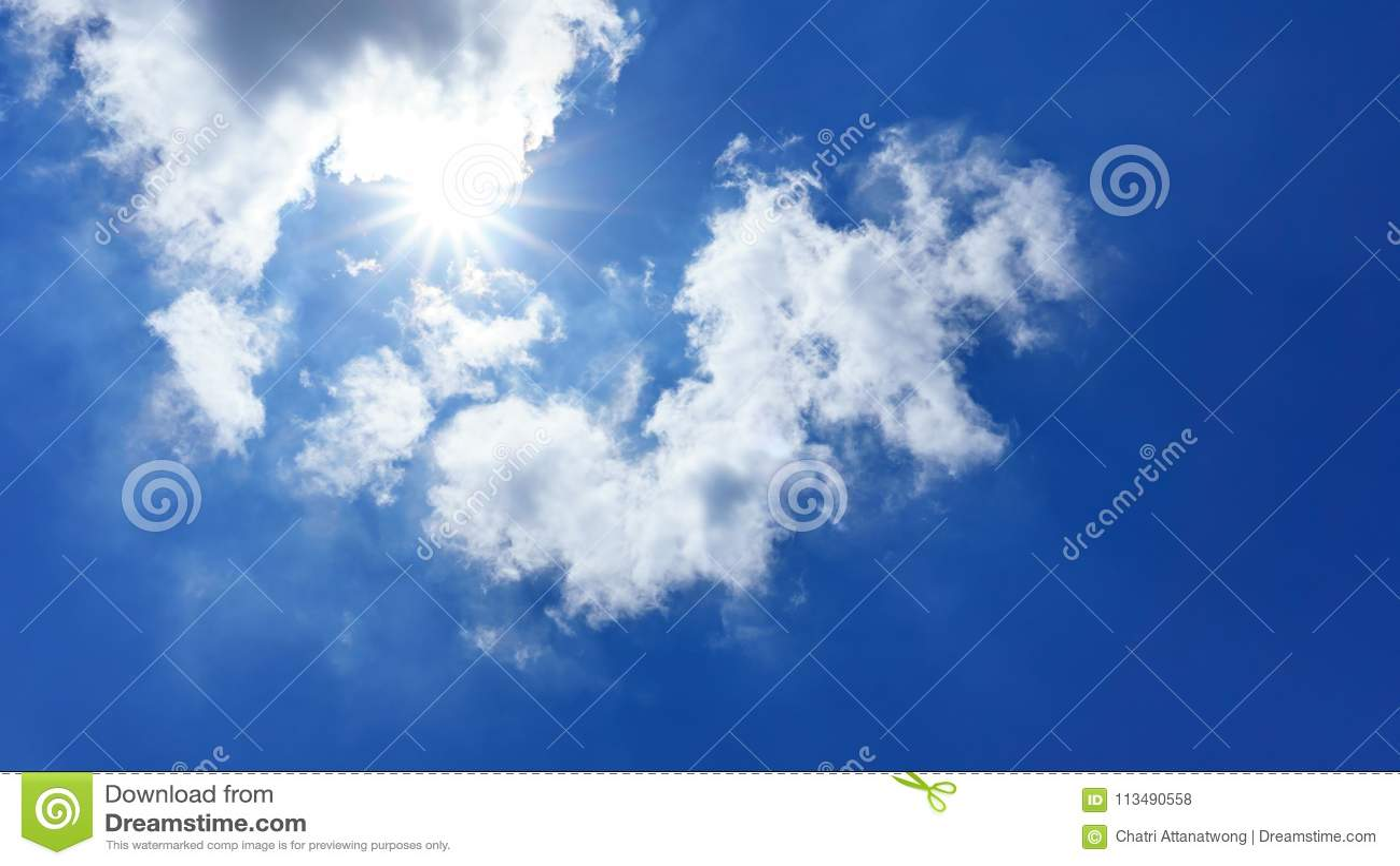 Le ciel bleu et le soleil est brillant derrière le cumulus pelucheux