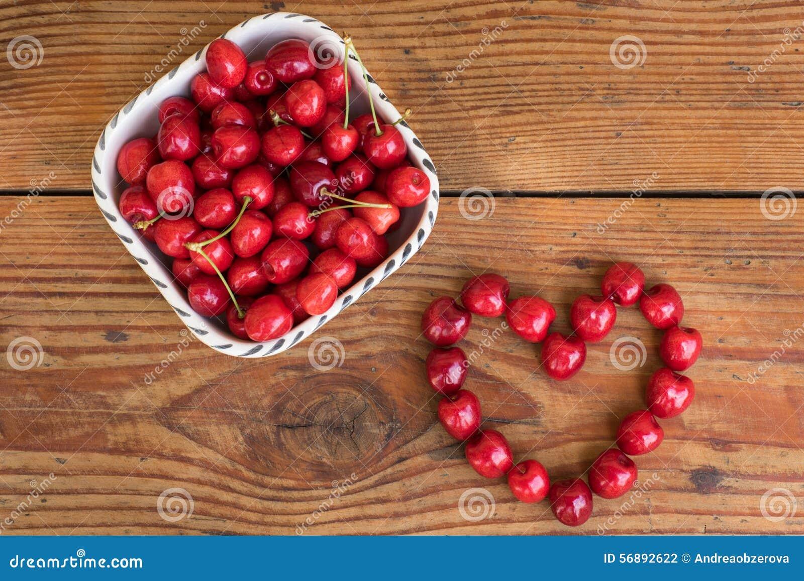 Le ciliege nostrane organiche su fondo di legno nel cuore modellano