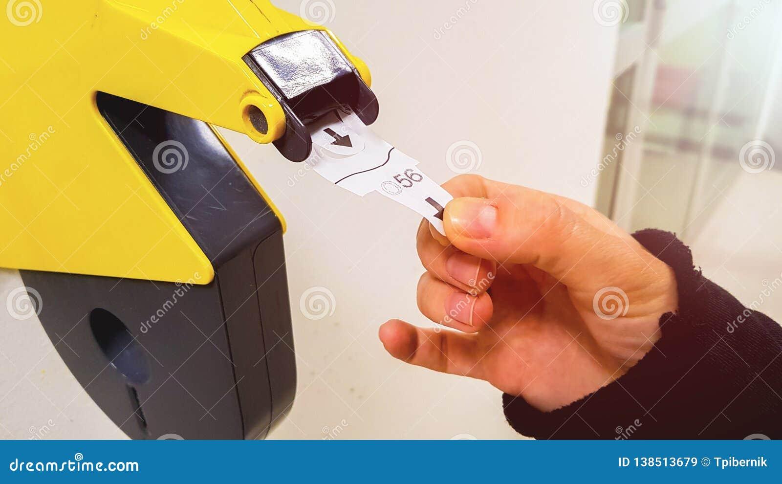 Le client tire avec la main un billet numéroté hors de la machine jaune de distributeur de nombre, pour attendre dans le tuyau de