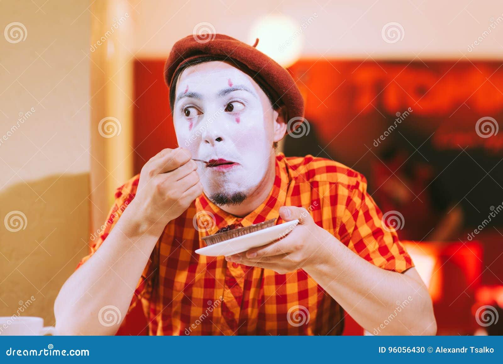 Le clown mange un gâteau dans un café et son visage coasse